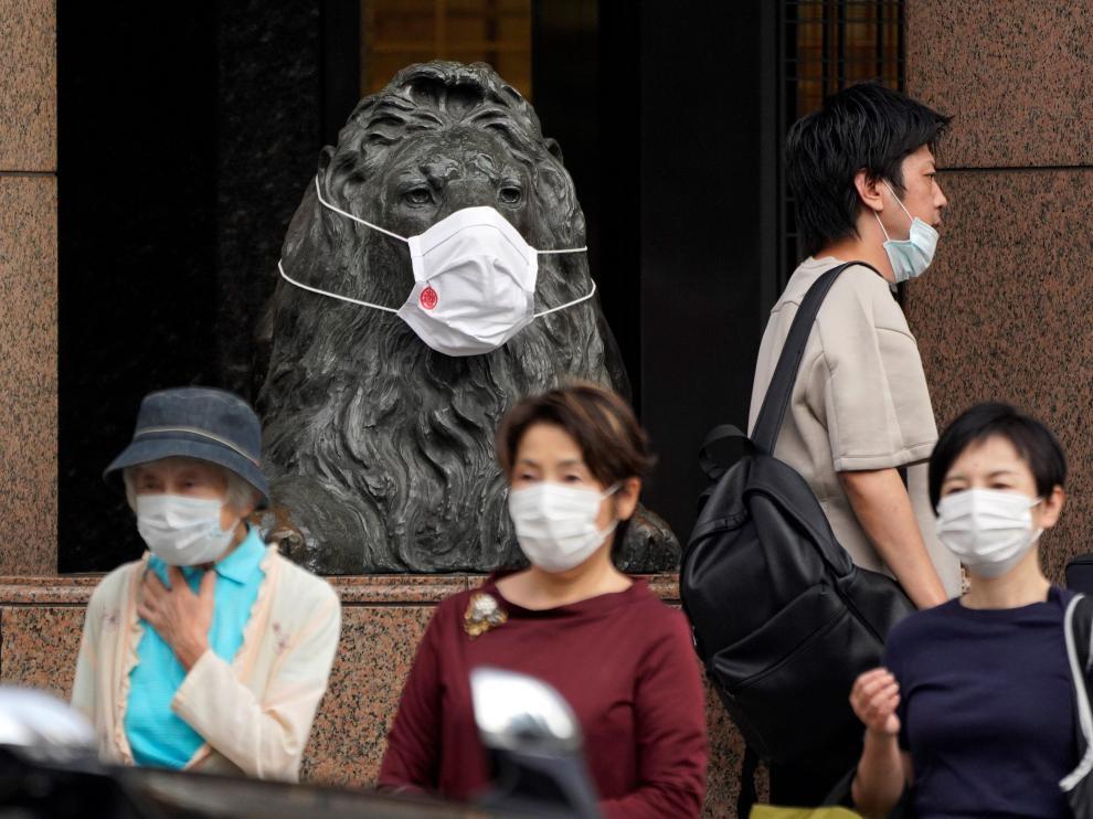 Tokiotas, junto a la figura de un león. símbolo de la ciudad.