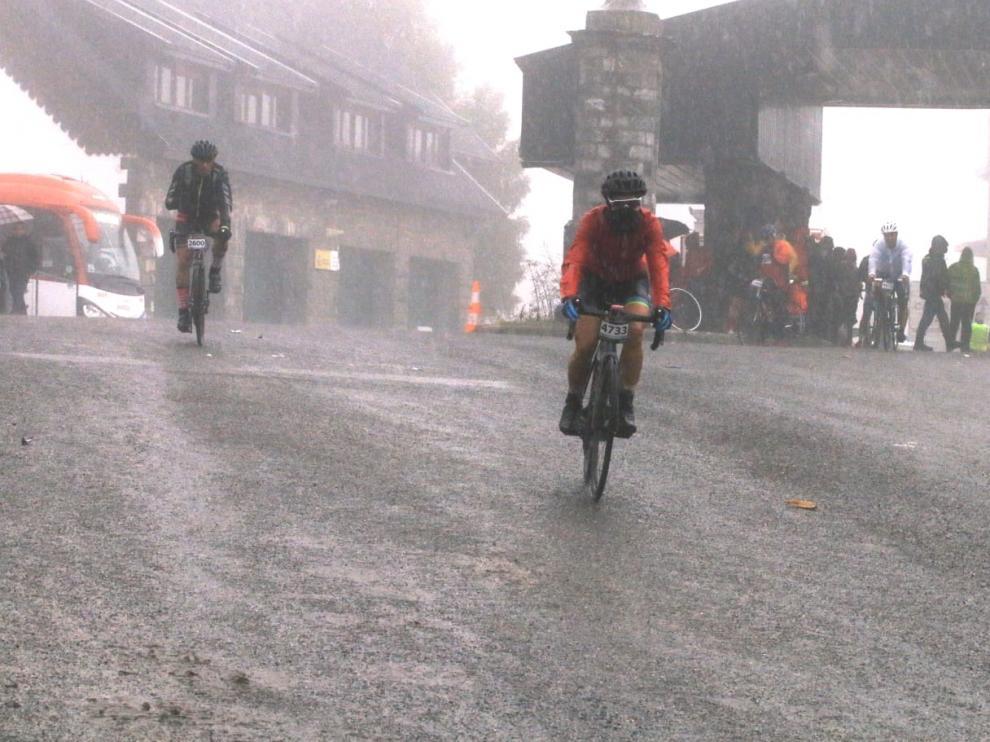 Los primeros ciclistas llegan a la frontera del Somport con la lluvia como protagonista de la jornada.