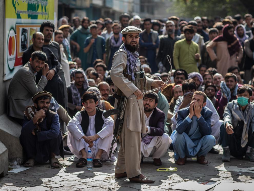 Un talibán, delante de un grupo de hombres que esperan que abra un banco para sacar dinero, en Kabul