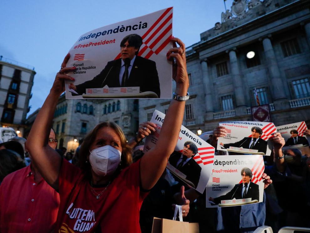 Una mujer sostiene un cartel de apoyo a Puigdemont en una concentración este viernes en Barcelona.
