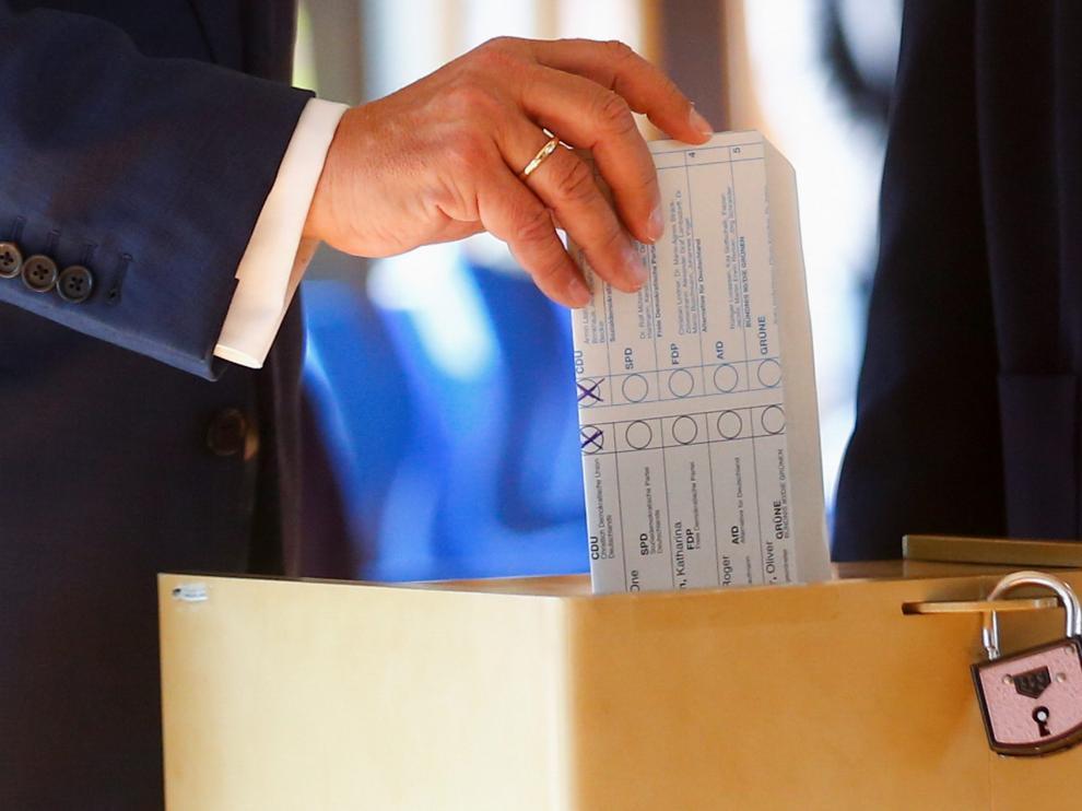 Armin Laschet introduce en la urna su papeleta doblada al revés.