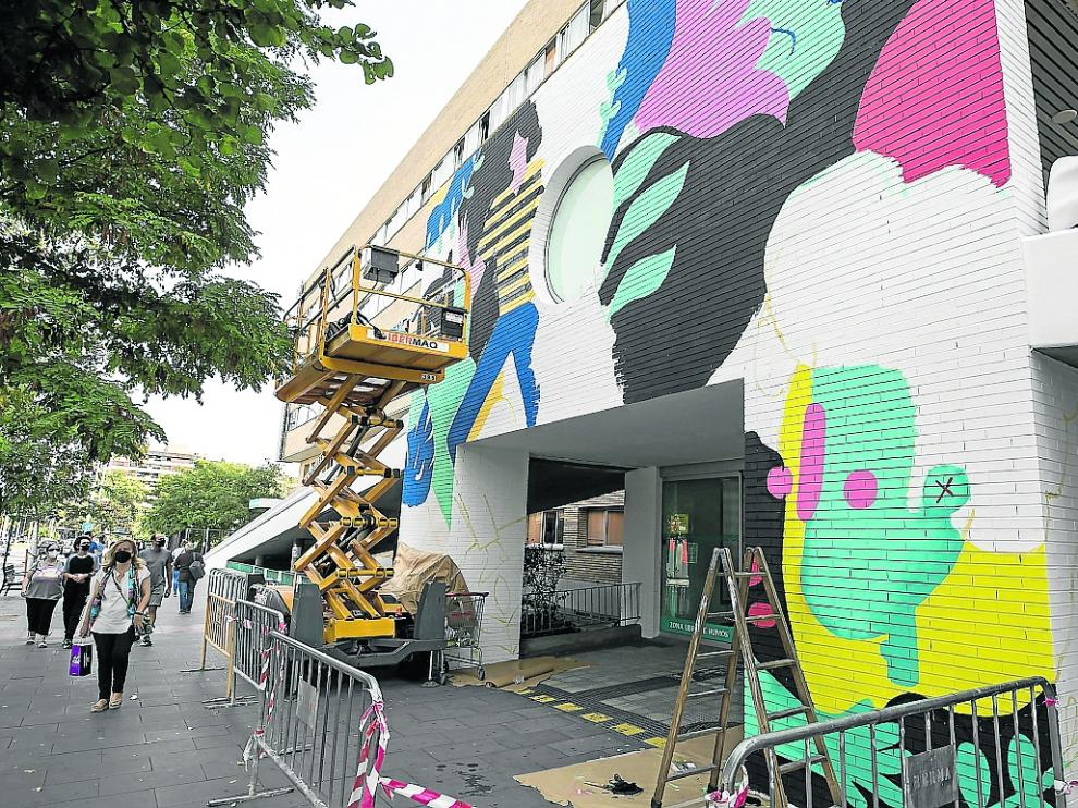 Proceso de creación del gran mural que plasman los artistas en la fachada del Infantil