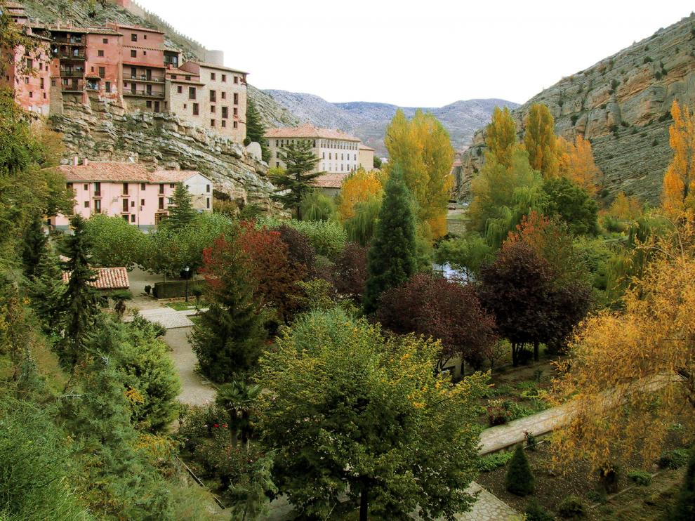 Arriba, vista de la localidad desde la zona baja, junto al río.