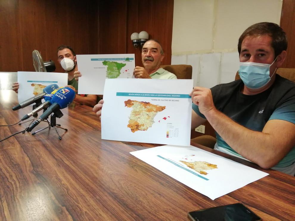 De izquierda a derecha, César Izquierdo, Ricardo Plumed y Francisco Ramo, de la plataforma Agrigate, muestran el mapa de reparto de ayudas. En color claro, las provincias cuyos agricultores percibirán menos dinero.