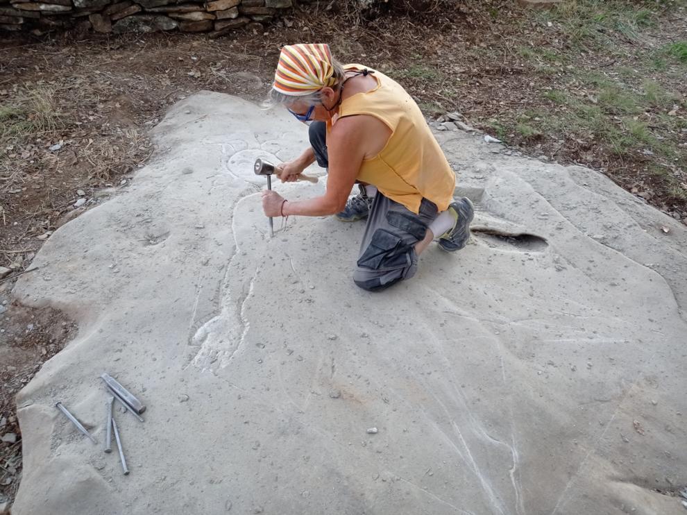 La escultora Sandrine Reynaud desarrolla un grabado al pie de los muros.