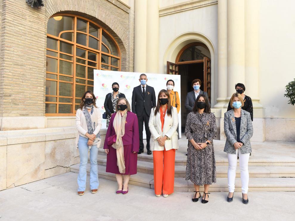 Miembros de Asapme, los premiados, la consejera de Sanidad y representantes institucionales, antes de acceder a la Sala de la Corona del Pignatelli.