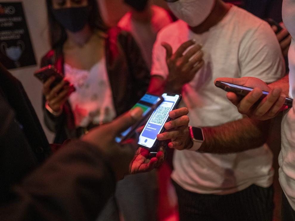 Una persona muestra su pasaporte covid en la entrada de una discoteca.