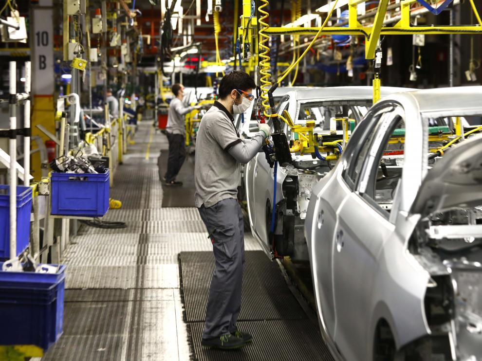 Operarios trabajando en la línea de montaje de la factoría zaragozana de PSA (Grupo Stellantis)