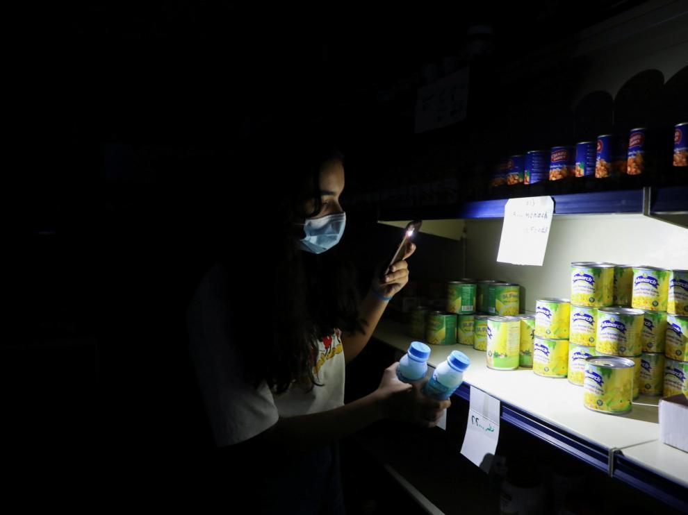 Una joven compra en un supermercado ayudada por la linterna de su móvil