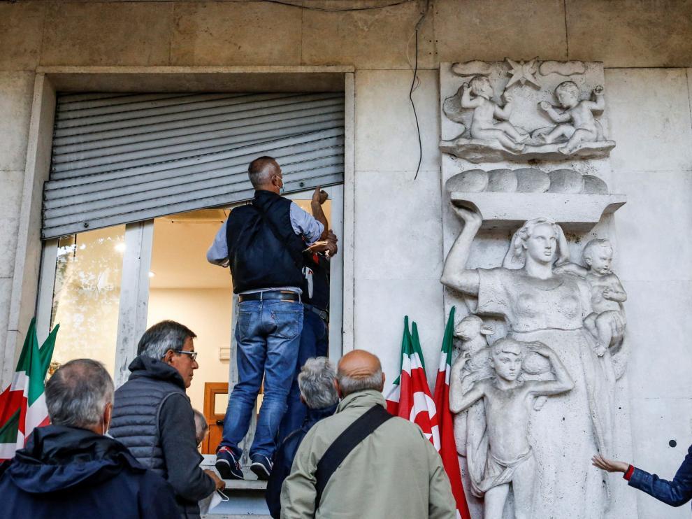 Varias personas arreglando los desperfectos de la sede del sindicato CGIL ITALY CLASHES AFTERMATH