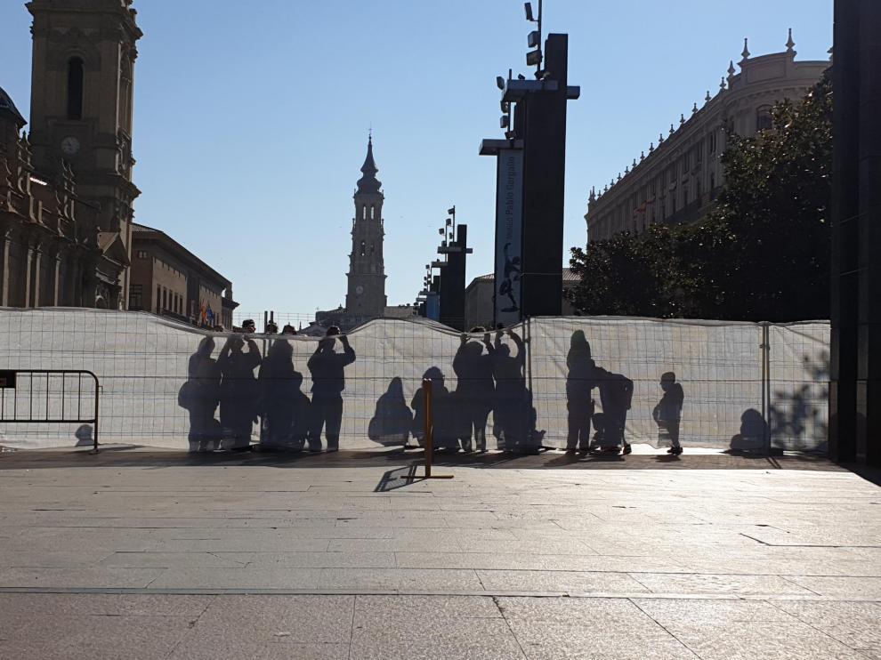 Varios curiosos intentando fotografiar a la Virgen por encima de las mallas