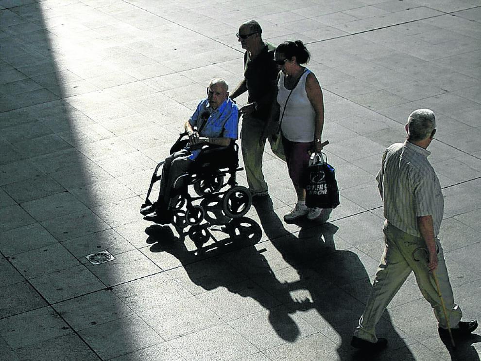 Unos pensionistas pasean por Sevilla.