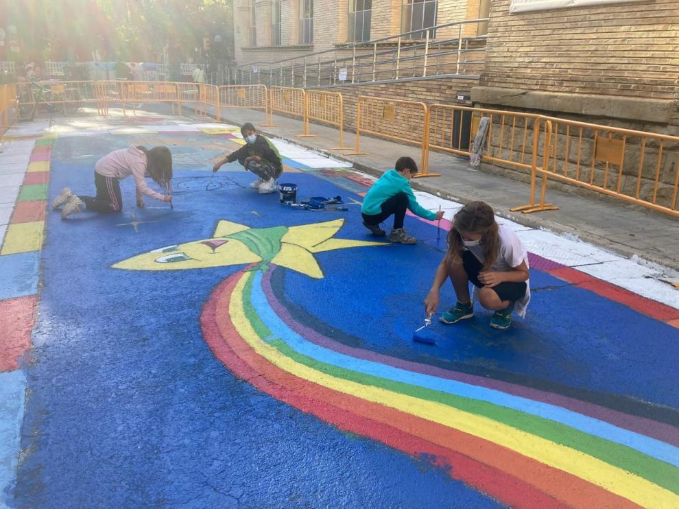 Miembros del Consejo de la Ciudad de las Niñas y los Niños de Huesca, pintando una calle peatonal.