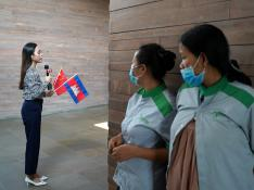 Airport cleaners in face masks observe a Cambodian TV reporter as a plane arrives from China to Cambodia with supplies and doctors donated to contain the spread of the coronavirus disease (COVID-19) outbreak